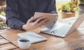 Επιχειρηματίας που χρησιμοποιεί την ταμπλέτα που λειτουργεί με το lap-top και τον καφέ Στοκ φωτογραφία με δικαίωμα ελεύθερης χρήσης