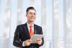 Επιχειρηματίας που χρησιμοποιεί την ταμπλέτα του στο γραφείο στοκ εικόνες