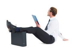 Επιχειρηματίας που χρησιμοποιεί την ταμπλέτα με τα πόδια επάνω στο χαρτοφύλακα Στοκ εικόνα με δικαίωμα ελεύθερης χρήσης