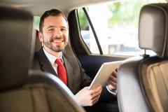 Επιχειρηματίας που χρησιμοποιεί την ταμπλέτα σε ένα αυτοκίνητο Στοκ Εικόνες