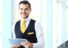 Επιχειρηματίας που χρησιμοποιεί την ταμπλέτα του στην αρχή Στοκ εικόνα με δικαίωμα ελεύθερης χρήσης