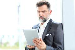 Επιχειρηματίας που χρησιμοποιεί την ταμπλέτα του στο γραφείο Στοκ φωτογραφίες με δικαίωμα ελεύθερης χρήσης