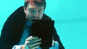 Επιχειρηματίας που χρησιμοποιεί την ταμπλέτα του υποβρύχια απόθεμα βίντεο