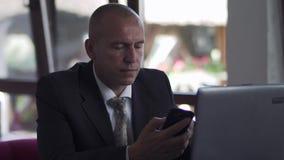 Επιχειρηματίας που χρησιμοποιεί την τηλεφωνική συνεδρίασή του στον πίνακα στον καφέ στο μεσημεριανό γεύμα απόθεμα βίντεο