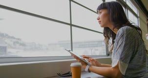 Επιχειρηματίας που χρησιμοποιεί την ψηφιακή ταμπλέτα κοντά στο παράθυρο σε ένα σύγχρονο γραφείο 4k απόθεμα βίντεο