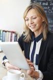 Επιχειρηματίας που χρησιμοποιεί την ψηφιακή ταμπλέτα στον καφέ Στοκ Φωτογραφίες