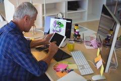 Επιχειρηματίας που χρησιμοποιεί την ψηφιακή ταμπλέτα στο γραφείο γραφείων Στοκ Φωτογραφίες