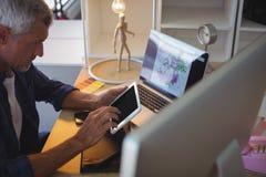 επιχειρηματίας που χρησιμοποιεί την ψηφιακή ταμπλέτα στο δημιουργικό γραφείο Στοκ φωτογραφία με δικαίωμα ελεύθερης χρήσης