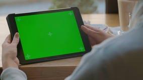 Επιχειρηματίας που χρησιμοποιεί τον υπολογιστή ταμπλετών με την πράσινη οθόνη αφής στον καφέ απόθεμα βίντεο