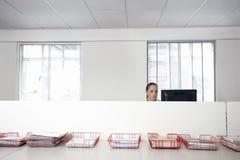 Επιχειρηματίας που χρησιμοποιεί τον υπολογιστή με τους δίσκους των εγγράφων σχετικά με τον πίνακα Στοκ Εικόνες