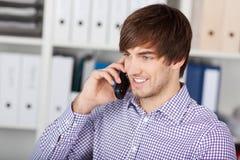 Επιχειρηματίας που χρησιμοποιεί το ασύρματο τηλέφωνο στην αρχή Στοκ εικόνα με δικαίωμα ελεύθερης χρήσης