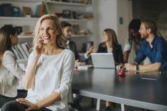 Επιχειρηματίας που χρησιμοποιεί το κινητό τηλέφωνο στην αρχή και το pe άλλων επιχειρήσεων Στοκ εικόνα με δικαίωμα ελεύθερης χρήσης