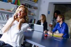 Επιχειρηματίας που χρησιμοποιεί το κινητό τηλέφωνο στην αρχή και το pe άλλων επιχειρήσεων Στοκ Εικόνες