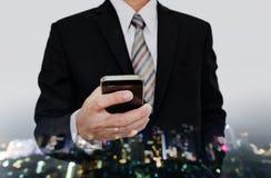 Επιχειρηματίας που χρησιμοποιεί το κινητό τηλέφωνο με τη εικονική παράσταση πόλης defocus τη νύχτα με το υπόβαθρο Bokeh Στοκ Εικόνα