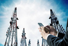 Επιχειρηματίας που χρησιμοποιεί το κινητό τηλέφωνο με τους πύργους τηλεπικοινωνιών με τις κεραίες TV και το δορυφορικό πιάτο Στοκ εικόνα με δικαίωμα ελεύθερης χρήσης