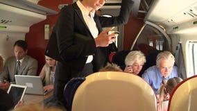 Επιχειρηματίας που χρησιμοποιεί το κινητό τηλέφωνο στην πολυάσχολη αμαξοστοιχία περιφερειακού σιδηροδρόμου απόθεμα βίντεο