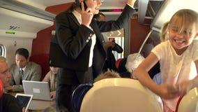 Επιχειρηματίας που χρησιμοποιεί το κινητό τηλέφωνο στην πολυάσχολη αμαξοστοιχία περιφερειακού σιδηροδρόμου φιλμ μικρού μήκους