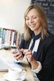 Επιχειρηματίας που χρησιμοποιεί το κινητό τηλέφωνο στον καφέ Στοκ Εικόνες
