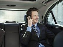 Επιχειρηματίας που χρησιμοποιεί το κινητό τηλέφωνο στο αυτοκίνητο Στοκ φωτογραφία με δικαίωμα ελεύθερης χρήσης