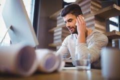 Επιχειρηματίας που χρησιμοποιεί το κινητό τηλέφωνο στο γραφείο υπολογιστών Στοκ Φωτογραφίες