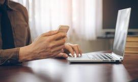 Επιχειρηματίας που χρησιμοποιεί το τηλέφωνο κυττάρων με το στην αρχή εκλεκτής ποιότητας τόνο εργασίας lap-top Στοκ φωτογραφία με δικαίωμα ελεύθερης χρήσης