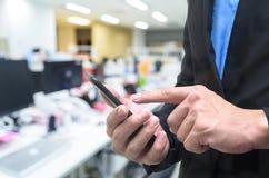 Επιχειρηματίας που χρησιμοποιεί το τηλέφωνο στο γραφείο εργασίας στοκ εικόνες