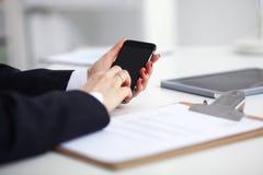 Επιχειρηματίας που χρησιμοποιεί το τηλέφωνό της στη συνεδρίαση γραφείων στο γραφείο, εκλεκτική εστίαση Στοκ εικόνες με δικαίωμα ελεύθερης χρήσης