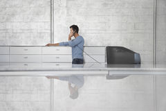 Επιχειρηματίας που χρησιμοποιεί το τηλέφωνο γραμμών εδάφους στην αρχή Στοκ Εικόνες