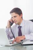 Επιχειρηματίας που χρησιμοποιεί το τηλέφωνο και το lap-top στο γραφείο Στοκ εικόνες με δικαίωμα ελεύθερης χρήσης