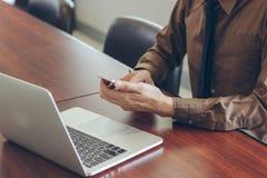 Επιχειρηματίας που χρησιμοποιεί το τηλέφωνο κυττάρων με την εργασία lap-top στην αρχή Στοκ Φωτογραφία