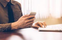Επιχειρηματίας που χρησιμοποιεί το τηλέφωνο κυττάρων με το στην αρχή εκλεκτής ποιότητας τόνο εργασίας lap-top Στοκ Εικόνες