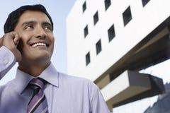 Επιχειρηματίας που χρησιμοποιεί το τηλέφωνο κυττάρων μπροστά από το κτίριο γραφείων Στοκ Εικόνες
