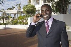Επιχειρηματίας που χρησιμοποιεί το τηλέφωνο κυττάρων μπροστά από το ξενοδοχείο Στοκ Φωτογραφίες