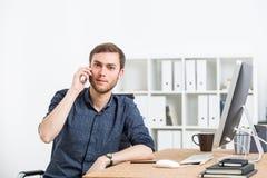 Επιχειρηματίας που χρησιμοποιεί το τηλέφωνο κυττάρων στην αρχή Στοκ Φωτογραφία