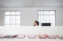 Επιχειρηματίας που χρησιμοποιεί το τηλέφωνο με τους δίσκους των εγγράφων σχετικά με τον πίνακα Στοκ εικόνα με δικαίωμα ελεύθερης χρήσης