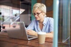 Επιχειρηματίας που χρησιμοποιεί το τηλέφωνο που λειτουργεί στο lap-top στη καφετερία Στοκ φωτογραφία με δικαίωμα ελεύθερης χρήσης