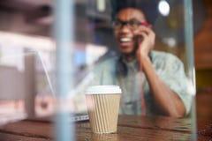 Επιχειρηματίας που χρησιμοποιεί το τηλέφωνο που λειτουργεί στο lap-top στη καφετερία Στοκ εικόνα με δικαίωμα ελεύθερης χρήσης