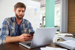 Επιχειρηματίας που χρησιμοποιεί το τηλέφωνο που λειτουργεί στο lap-top στην αρχή Στοκ φωτογραφία με δικαίωμα ελεύθερης χρήσης