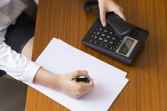 Επιχειρηματίας που χρησιμοποιεί το τηλέφωνο, που παίρνει τις σημειώσεις στο γραφείο γραφείων Στοκ Φωτογραφία