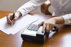 Επιχειρηματίας που χρησιμοποιεί το τηλέφωνο, που παίρνει τις σημειώσεις στο γραφείο γραφείων Στοκ Εικόνες