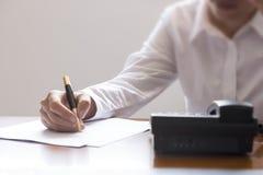 Επιχειρηματίας που χρησιμοποιεί το τηλέφωνο, που παίρνει τις σημειώσεις στο γραφείο γραφείων Στοκ φωτογραφία με δικαίωμα ελεύθερης χρήσης