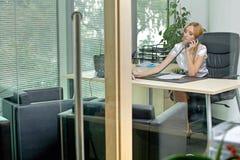 Επιχειρηματίας που χρησιμοποιεί το τηλέφωνο στο γραφείο Στοκ εικόνες με δικαίωμα ελεύθερης χρήσης