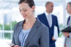 επιχειρηματίας που χρησιμοποιεί το τηλέφωνό της με το συνάδελφο δύο πίσω από την Στοκ φωτογραφία με δικαίωμα ελεύθερης χρήσης