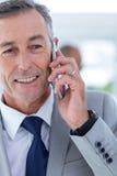 επιχειρηματίας που χρησιμοποιεί το τηλέφωνό της με το συνάδελφο δύο πίσω από τον Στοκ Εικόνες