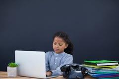 Επιχειρηματίας που χρησιμοποιεί το φορητό προσωπικό υπολογιστή στο μαύρο κλίμα Στοκ Φωτογραφία