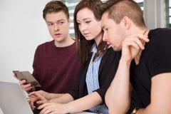 Επιχειρηματίας που χρησιμοποιεί το lap-top από τους συναδέλφους Στοκ Εικόνες