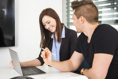Επιχειρηματίας που χρησιμοποιεί το lap-top από το συνάδελφο στο γραφείο Στοκ Εικόνες