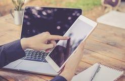 Επιχειρηματίας που χρησιμοποιεί το lap-top που λειτουργεί με την ταμπλέτα και το σημειωματάριο Στοκ Φωτογραφία