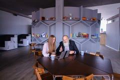 Επιχειρηματίας που χρησιμοποιεί το lap-top με τον παλαιό συνάδελφο ατόμων σε επιτυχή Στοκ Εικόνες