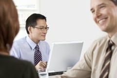 Επιχειρηματίας που χρησιμοποιεί το lap-top με τους συναδέλφους στο πρώτο πλάνο Στοκ φωτογραφίες με δικαίωμα ελεύθερης χρήσης